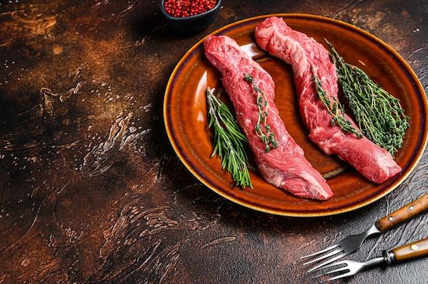 Stek z surowego mięsa wołowego na talerzu. ciemne tło. widok z góry. skopiuj miejsce.