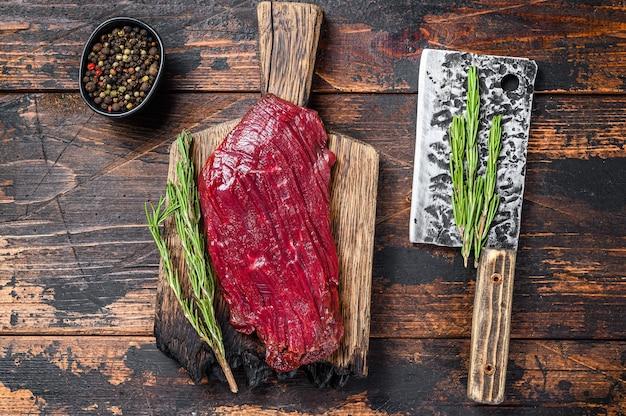 Stek z surowego mięsa z dziczyzny na desce cuuting z rozmarynem. czarne tło. widok z góry.