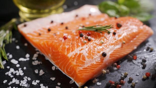 Stek z surowego pstrąga z łososia z czerwonej ryby z ziołami, cytryną i oliwą z oliwek rotowany na łupku
