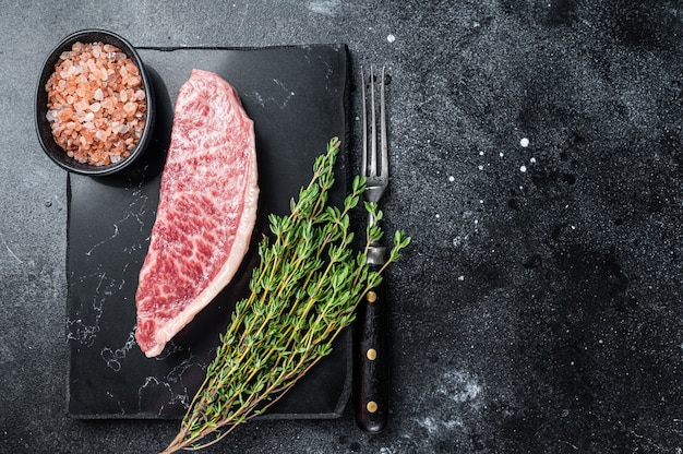 Stek z surowej polędwicy wagyu, mięso wołowe kobe na marmurowej desce. czarne tło. widok z góry. skopiuj miejsce.