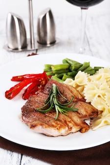 Stek z warzywami i makaronem na talerzu na drewnianym talerzu
