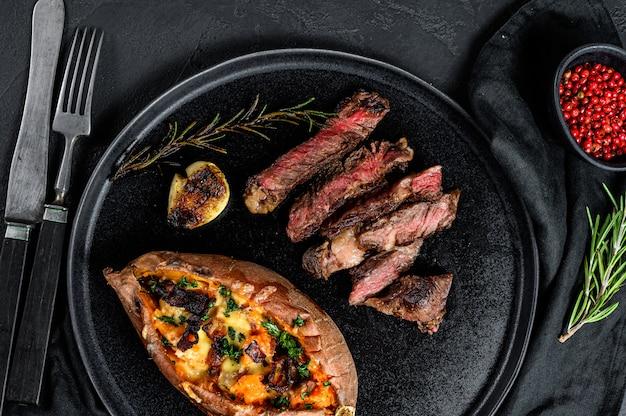 Stek z żeberka ozdobiony pieczonymi słodkimi ziemniakami. pieczeń wołowa. ekologiczne mięso rolnicze.