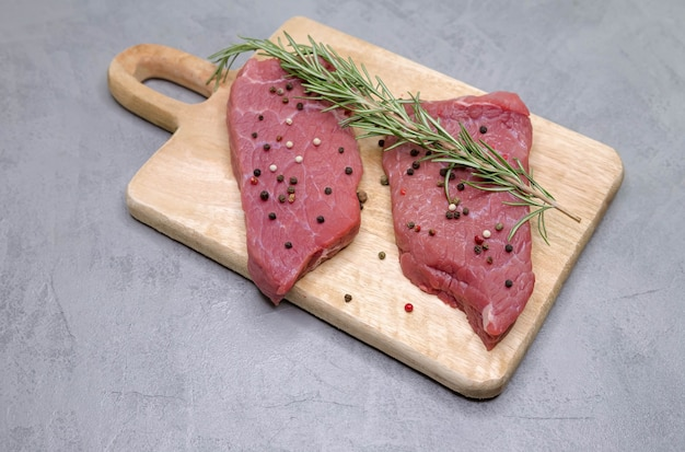 Stek z żeberka surowego mięsa na deska do krojenia. gotowanie filetów ze steków wołowych
