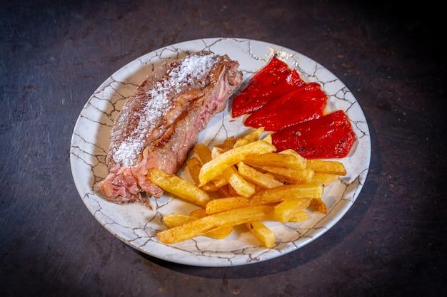 Stek z ziemniakami i czerwoną papryką na czarnym tle, na białym talerzu
