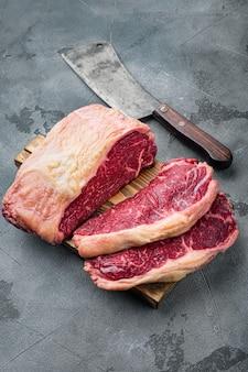 Stek żyłkowy, marmurkowe surowe mięso wołowe, na szarym stole