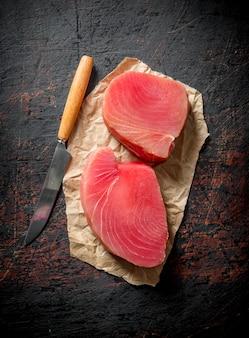 Steki świeżego surowego tuńczyka na papierze z nożem na rustykalnym stole