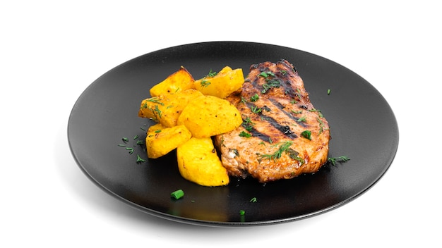 Steki wieprzowe w sosie i pieczone ziemniaki na talerzu na białym tle.