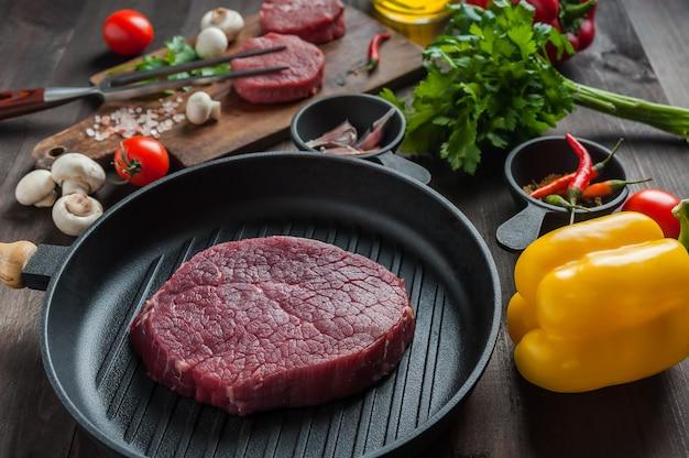 Steki wołowe gotowe do gotowania, tło kulinarne. świeże surowe mięso na drewnianej desce do krojenia