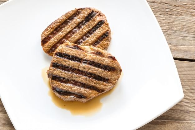 Steki wołowe na białym kwadratowym talerzu