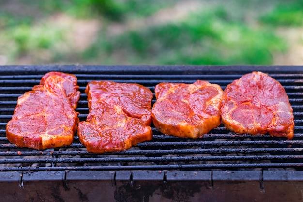 Steki wołowe na grillu z płomieniami.