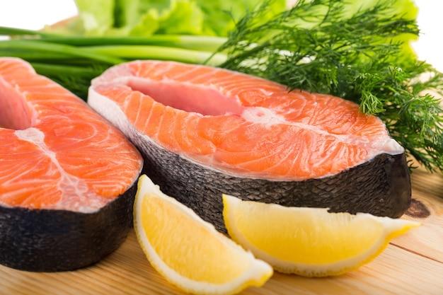 Steki z surowego łososia na desce do krojenia ze świeżymi ziołami i ćwiartkami cytryny