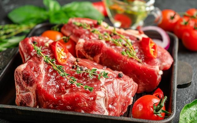 Steki z surowego mięsa czerwonego na patelni grillowej z przyprawami i ziołami