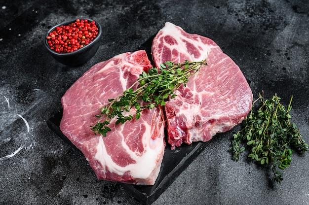 Steki z surowego mięsa wieprzowego na pokładzie marmuru