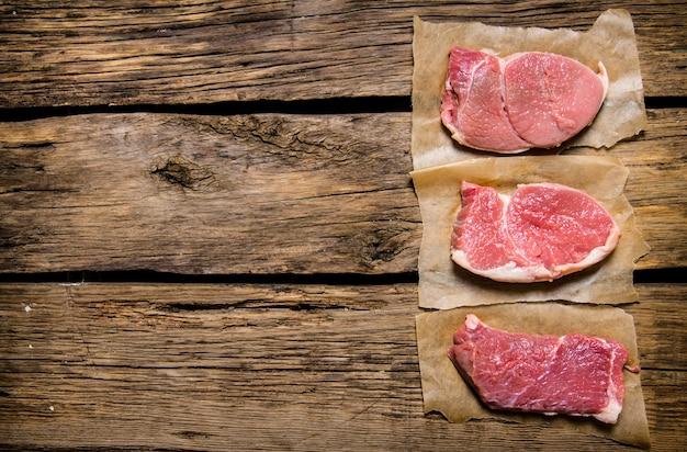 Steki z surowego świeżego mięsa. na drewnianym tle. wolne miejsce na tekst. widok z góry