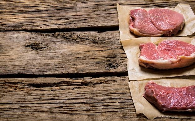 Steki z surowego świeżego mięsa. na drewnianym tle. wolne miejsce na tekst.
