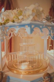 Stemplowa fontanna z światłami i żółtym napojem na stole.