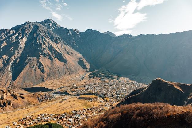 Stepantsminda, kazbegi, goergia. pejzaż dużego wiejskiego miasteczka z pasmem górskim kazbak.