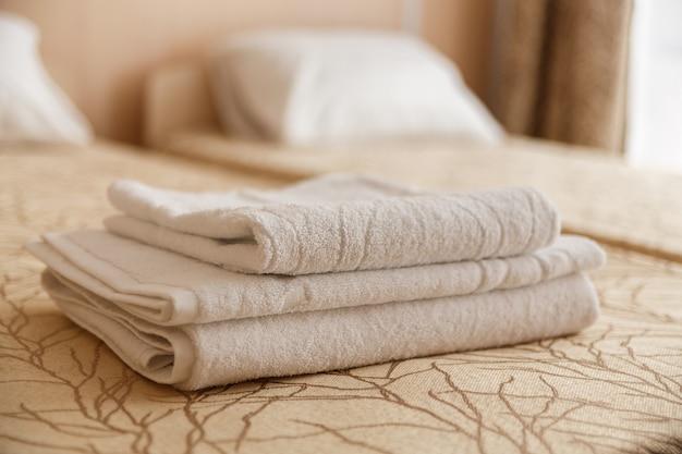Sterta biały hotelowy ręcznik na łóżku w sypialni wnętrzu.