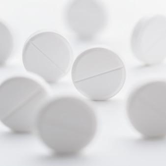 Sterta białych pigułek rozrzuconych na jasnej, białej powierzchni. selektywna ostrość.