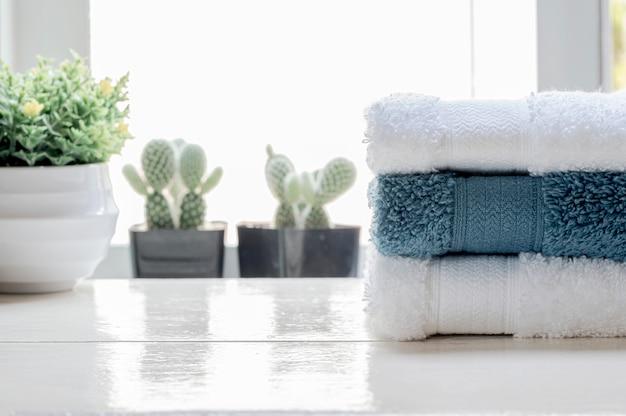 Sterta czyści ręczniki i houseplant na białym drewnianym stole.