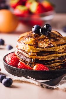 Sterta domowych naleśników z jagodami i truskawkami, idealna na śniadanie