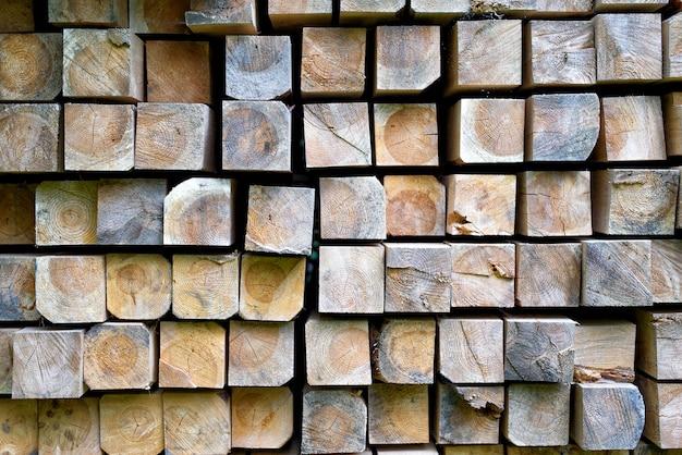 Sterta drewniani bary w magazynie. ułożone drewniane belki o przekroju kwadratowym