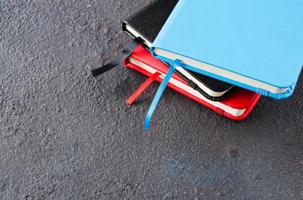 Sterta kolorowi notatniki dla pisać lub książki na ciemnym tle