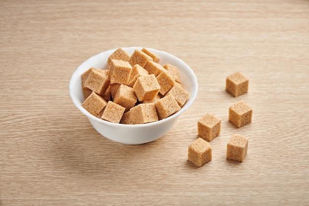 Sterta kostek brązowego cukru trzcinowego w misce na drewnianym stole w kuchni.