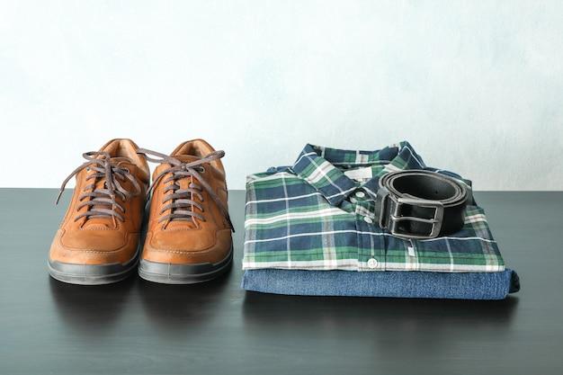 Sterta koszula, cajgi i pasek z butami na stole przeciw lekkiemu tłu, przestrzeń dla teksta