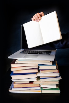 Sterta książek laptopu czerni tła notatnika ręka