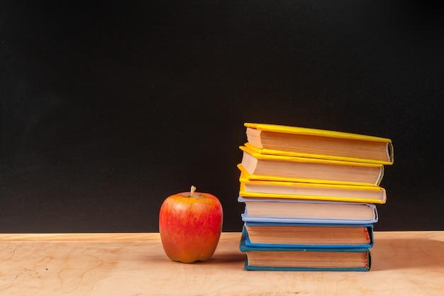 Sterta książki z jabłkiem i ołówkiem na stole