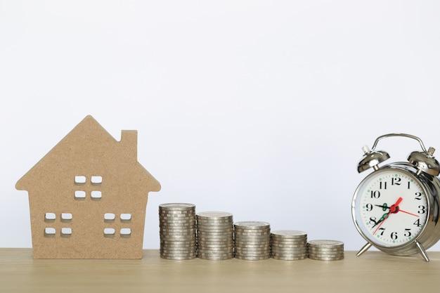 Sterta moneta pieniądze i modela dom na wtite tle