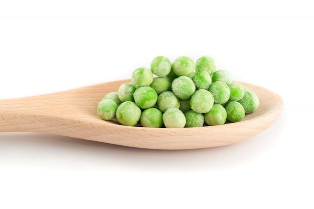 Sterta mrożonych słodkiego zielonego groszku w drewnianą łyżką na białym tle