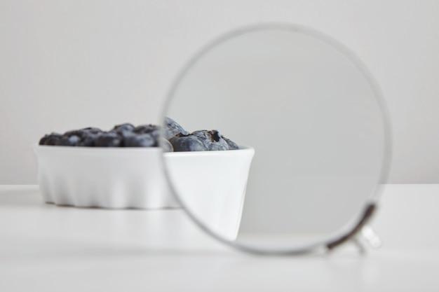 Sterta organicznego pożywienia przeciwutleniającego z jagodami w koncepcji ceramicznej miski do zdrowego odżywiania i odżywiania na białym stole, magnetyzowana przez lupę dwuokularową, aby zobaczyć szczegóły