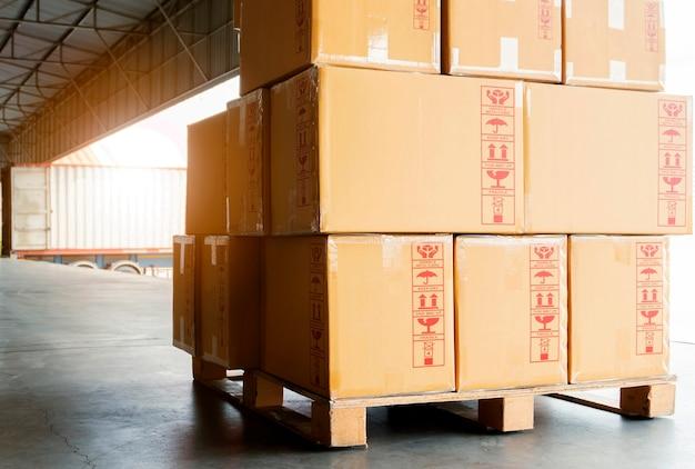 Sterta pakunków pudełka na drewnianej palecie przy magazynowym dokiem