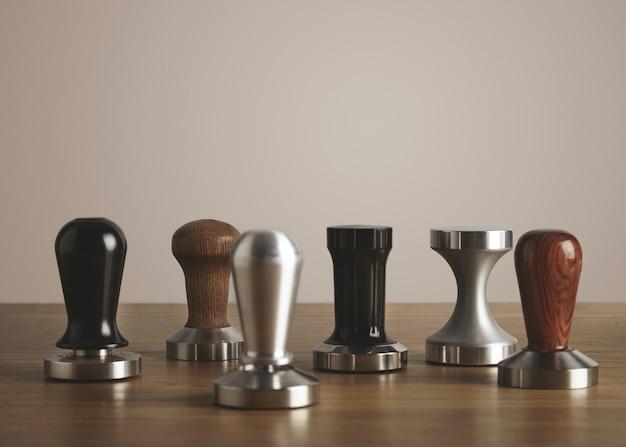 Sterta różnych ubijaków. profesjonalne narzędzia do parzenia kawy ze stali i drewna na grubym drewnianym stole na białym tle.