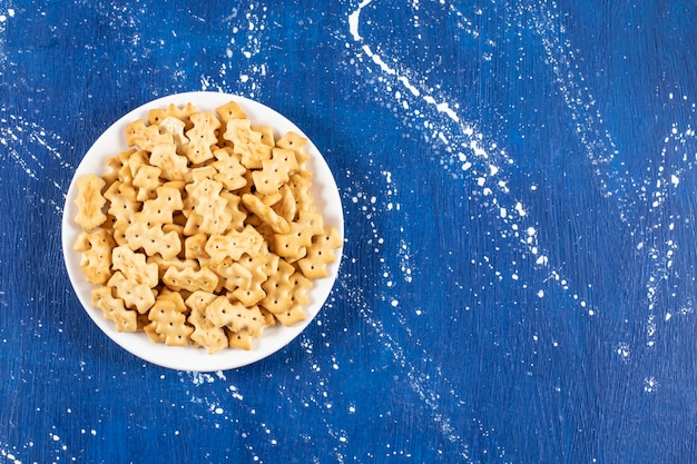 Sterta słonych małych krakersów umieszczona na białym talerzu