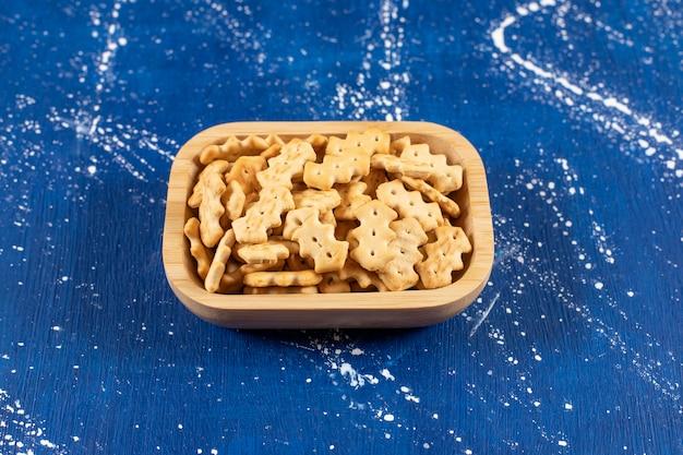 Sterta słonych małych krakersów umieszczona w drewnianej misce