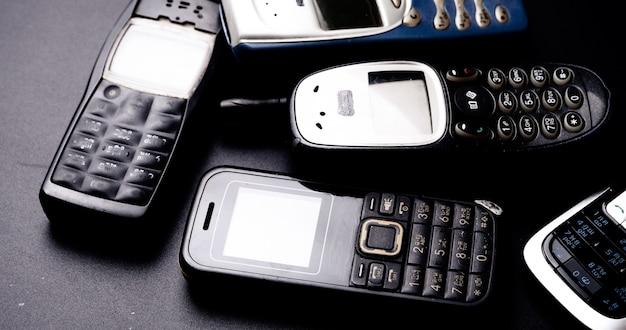 Sterta starych telefonów komórkowych na czarnym tle.