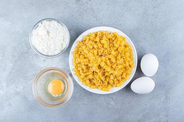 Sterta surowego makaronu rigate w białej misce z jajkami i mąką.