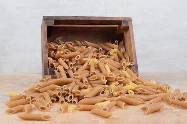 Sterta surowego makaronu w drewnianym koszu na marmurowej przestrzeni.