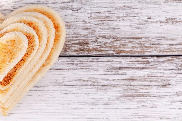 Sterta wznoszący toast chlebowi serca na drewnianym stole, pojęcie poparcie w dużej rodzinie