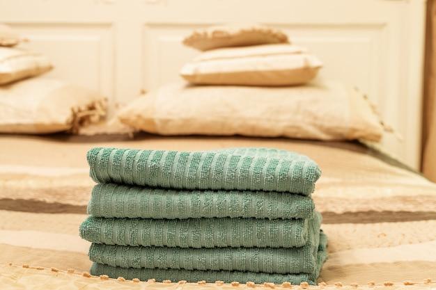 Sterta zielony hotelowy ręcznik na łóżku w sypialni wnętrzu