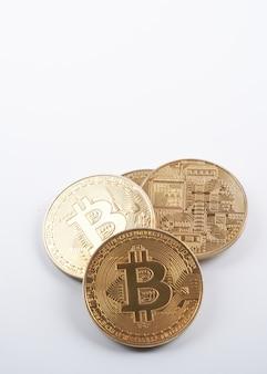 Sterta złotych bitcoinów na białym tle z bliska z miejsca na kopię