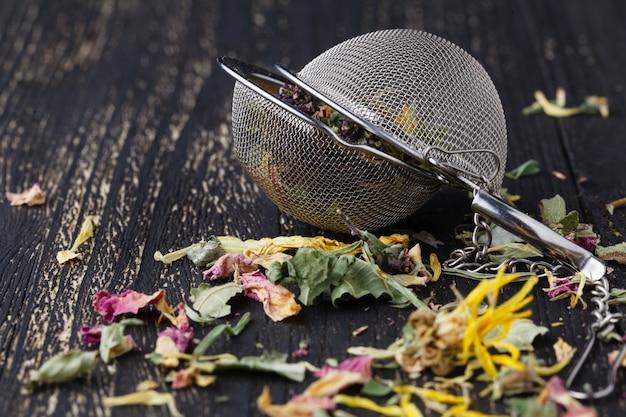 Sterty luźnej herbaty ziołowej na drewnianym stole