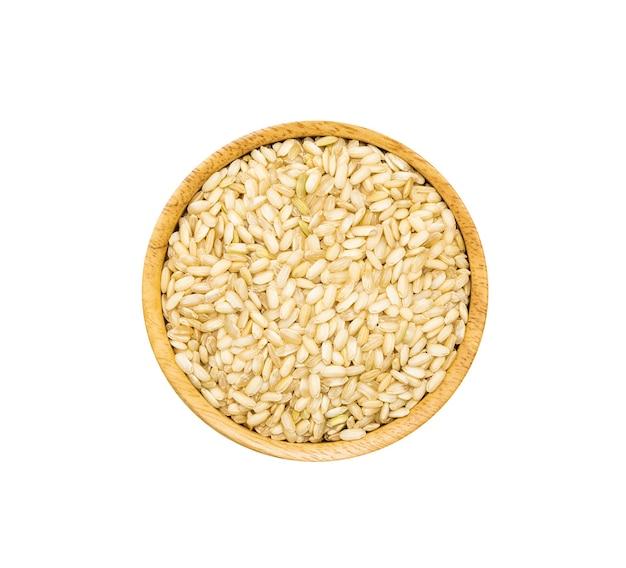 Sterty ryżu średnioziarnistego w drewnianej misce brązowy na białym tle, widok z góry. niepolerowane organiczne ziarno brązowego ryżu z kiełkami