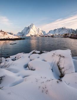 Sterty śniegu z wioski rybackiej w snowy góry na wybrzeżu. lofoty, norwegia