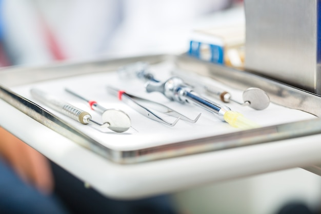 Sterylne narzędzia lub instrumenty medyczne dla dentysty, lusterka, pinceta i strzykawka do znieczulenia miejscowego w gabinecie dentystycznym
