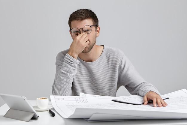 Stess, przepracowanie i termin. zmęczony, nieogolony młody architekt masuje mostek nosa