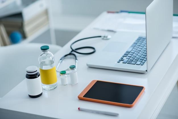 Stetoskop, butelki z lekarstwami i urządzeniami na stole